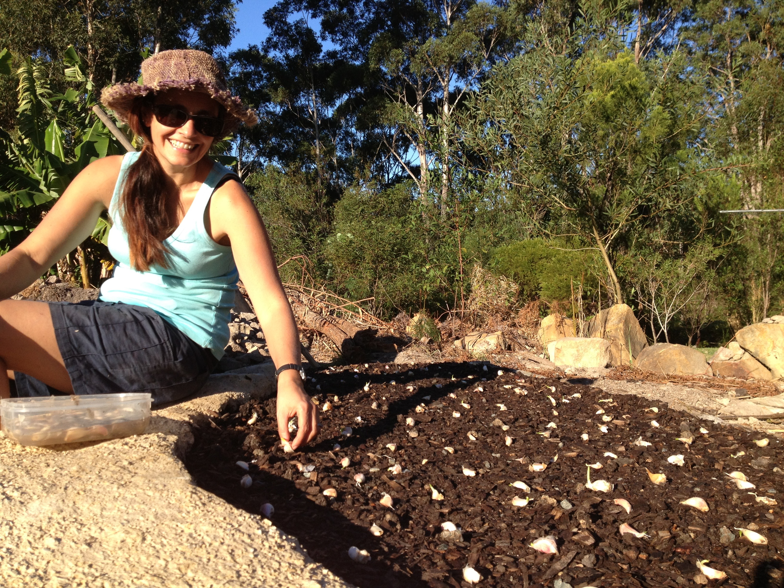 Megan Cooke planting cloves of Garlic at Garden to Table Permaculture